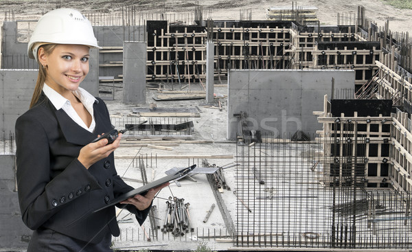 Beautiful businesswoman in helmet holding paper holder and portable radio. Construction site as back Stock photo © cherezoff