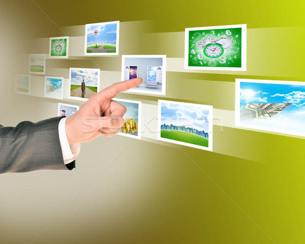 Businessman touching holographic pictures Stock photo © cherezoff