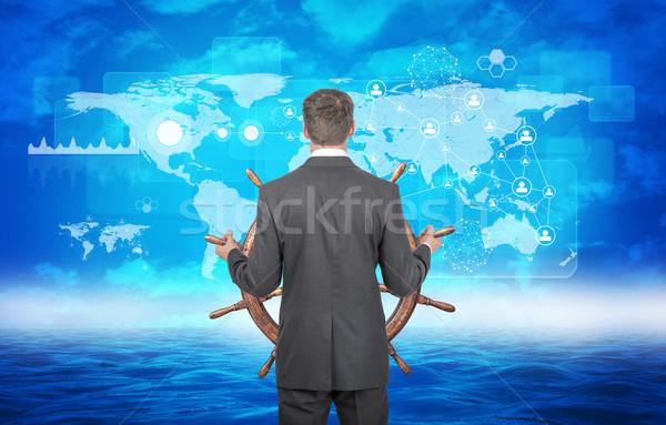 Férfi kormánykerék tenger üzletember tart világtérkép Stock fotó © cherezoff