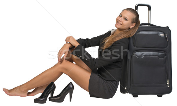 Businesswoman with her shoes off sitting next to front view suitcase Stock photo © cherezoff