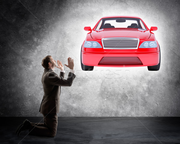 Businessman on knees in front of car Stock photo © cherezoff