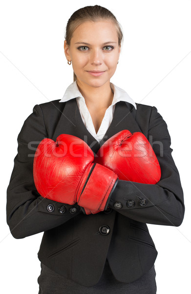 Businesswoman wearing boxing gloves, arms crossed on her breast Stock photo © cherezoff