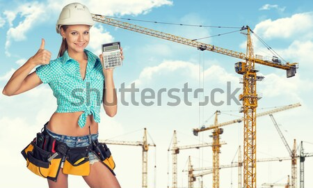 Stock photo: Woman in tool belt holding helmet under his arm. Looking at camera, smiling. Construction site as ba