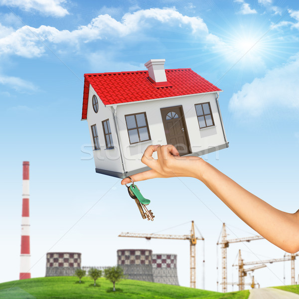 Hand holding house and bunch of keys. In background tower crane, chimney, green hill with grass, tre Stock photo © cherezoff