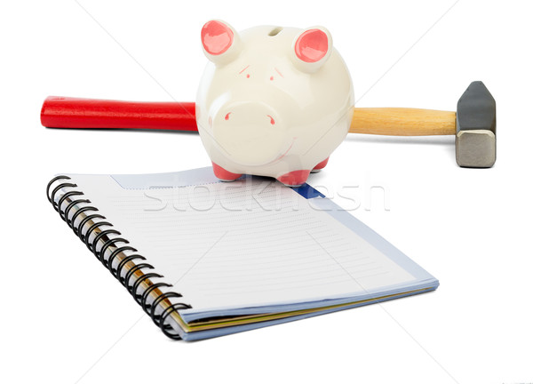 Piggy bank with hammer and pad on white Stock photo © cherezoff