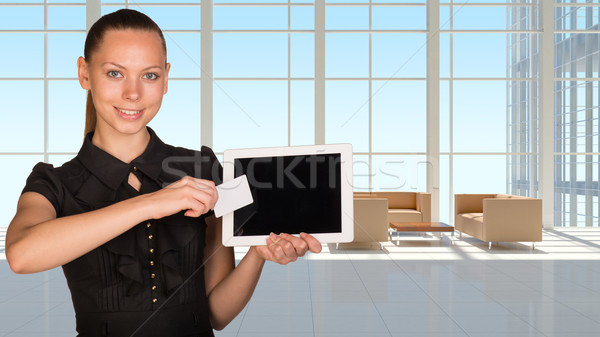 Beautiful businesswoman holding tablet PC. White roomy hall with sofas and coffee table as backdrop Stock photo © cherezoff