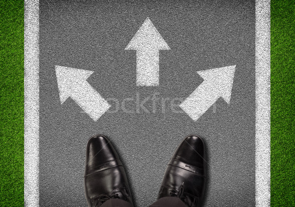Stock photo: Top view. Shoes standing on asphalt road with white lines and arrows