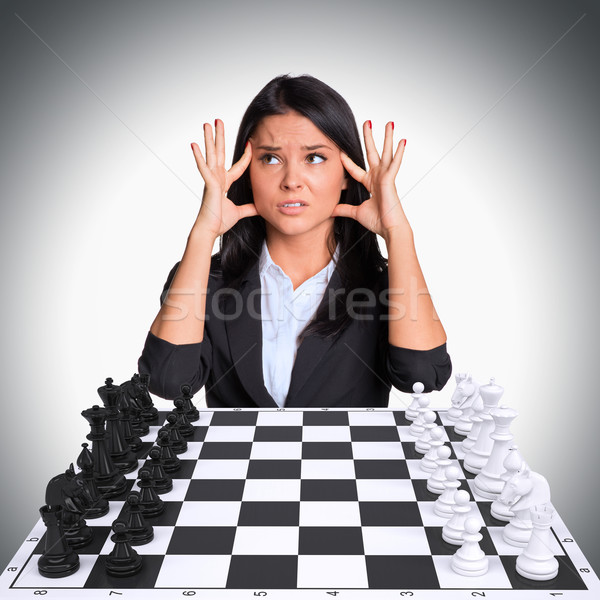 Lost in thought woman looking up. Chessboard with chess Stock photo © cherezoff