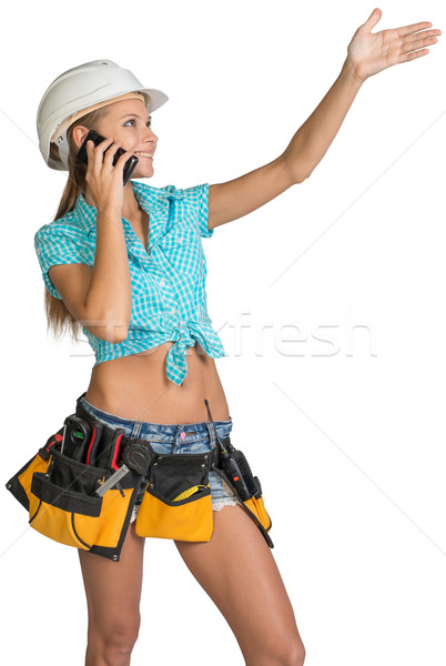 Woman in hard hat calling on mobile phone and showing direction Stock photo © cherezoff