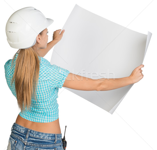 Beautiful woman builder holding in front of him large paper sheet. Rear view Stock photo © cherezoff