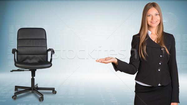 Businesswoman showing something or copyspase for product. Office chair beside Stock photo © cherezoff
