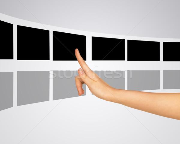 Woman pressing virtual photo within right pointer finger Stock photo © cherezoff