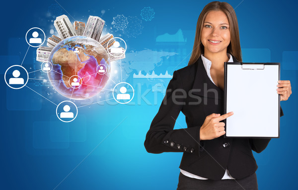 Beautiful businesswoman holding paper holder. Earth with buildings and network Stock photo © cherezoff
