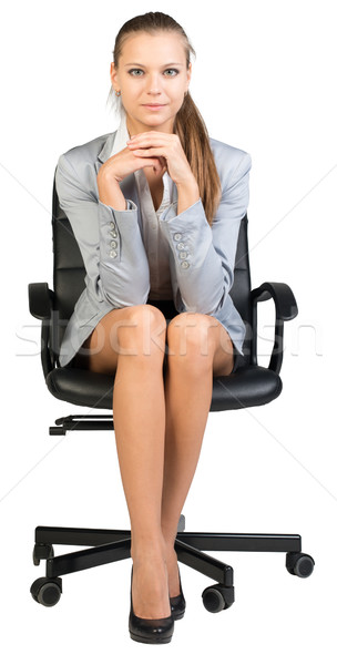 Businesswoman on office chair, with hands clasped under her chin Stock photo © cherezoff