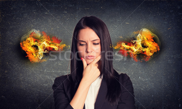 Thoughtful woman with fire from ears. Concrete gray wall as backdrop Stock photo © cherezoff