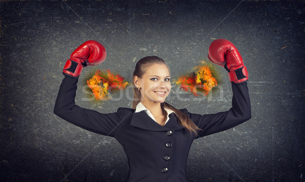 Confident woman in red gloves with fire from ears. Concrete gray wall as backdrop Stock photo © cherezoff