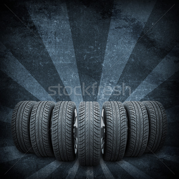 Wedge of new car wheels. Background is concrete surface and stripes at bottom Stock photo © cherezoff