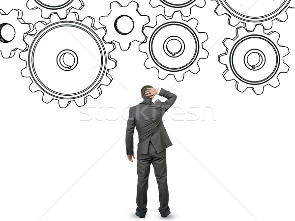 Confused businessman in front of cog wheels Stock photo © cherezoff
