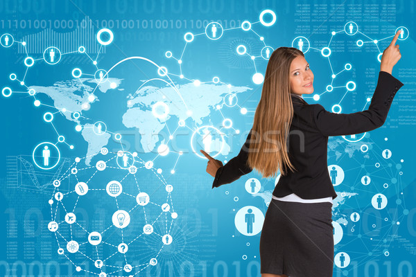Beautiful businesswoman in suit presses fingers virtual network contacts Stock photo © cherezoff
