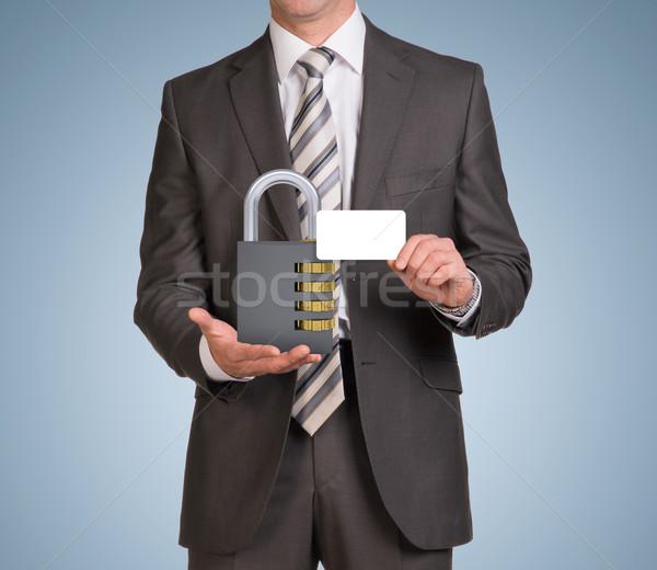 Businessman hold empty card and combination lock Stock photo © cherezoff
