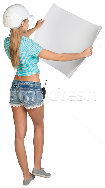 Woman in hard hat showing blank sheet of drawing paper. Rear view Stock photo © cherezoff