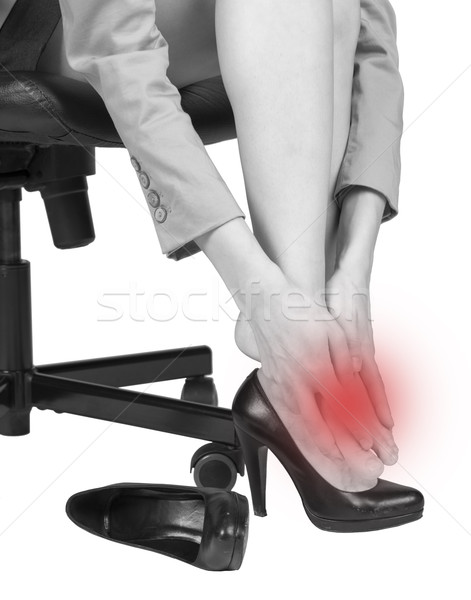 Businesswoman massaging her aching foot Stock photo © cherezoff