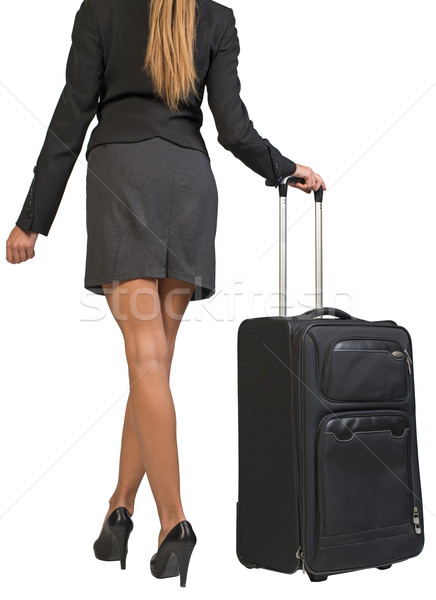 Cropped image of businesswoman with wheeled travel bag makes step forward, back view Stock photo © cherezoff