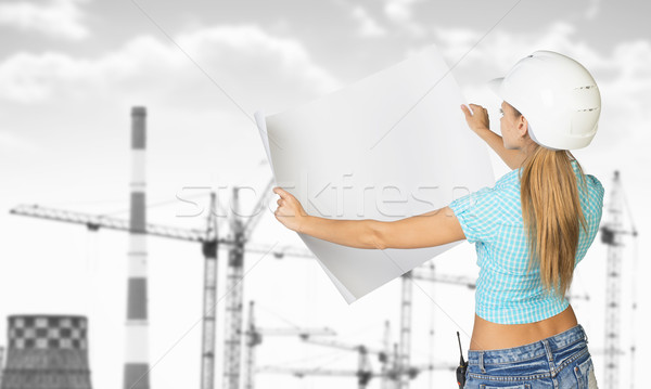 Woman in helmet standing backwards and holding paper sheet. Gray tower cranes as backdrop Stock photo © cherezoff