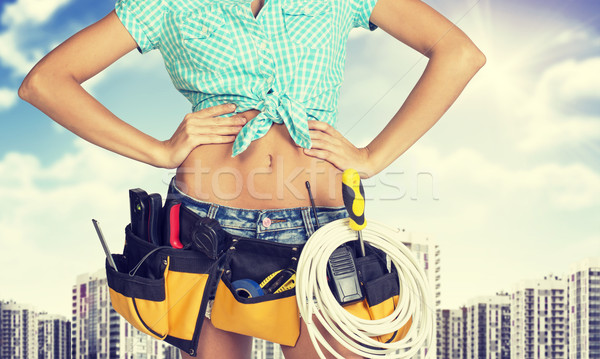 Woman in tool belt standing akimbo. Cropped image. High-rise buildings as backdrop Stock photo © cherezoff