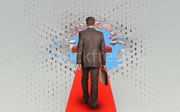 Businessman walking on arrow pierced brick wall Stock photo © cherezoff