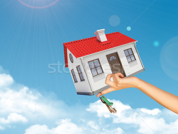 House and keys in womans left hand under clouds Stock photo © cherezoff