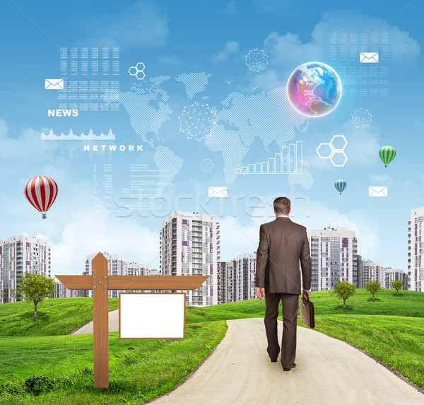 Businessman walking along road running through green hills towards city.  Brightly coloured planet,  Stock photo © cherezoff