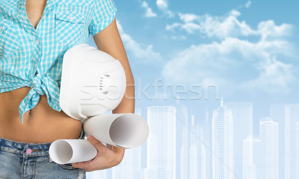 Woman holding helmet and paper scrolls. Cropped image. Wire-frame buildings as backdrop Stock photo © cherezoff