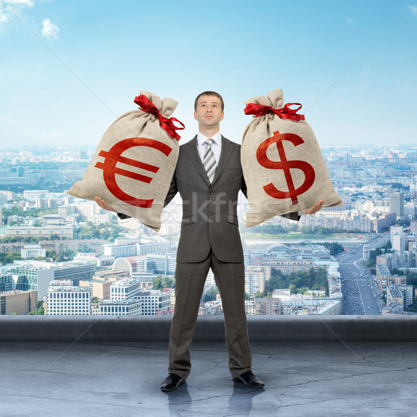 Man holding moneybags with dollar and euro signs Stock photo © cherezoff