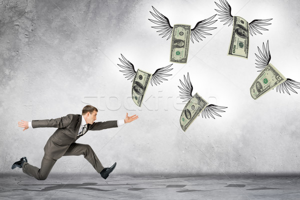 Business man running to catch flying dollars Stock photo © cherezoff