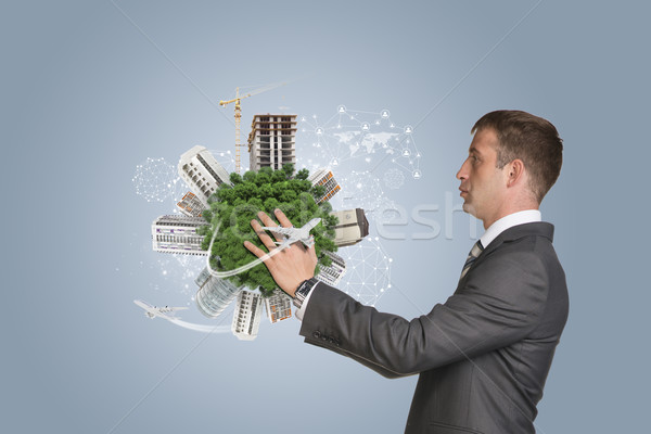 Businessman hold Earth with buildings Stock photo © cherezoff