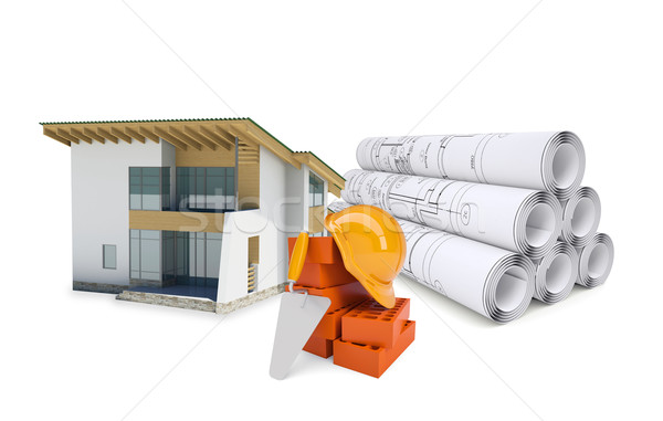 Stock photo: Small model house near scrolls of architectural drawings and work tools
