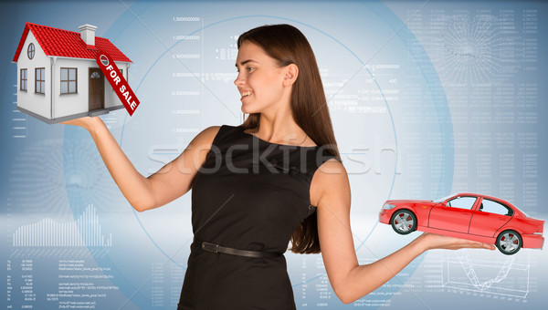 Smiling businesslady holding car and house Stock photo © cherezoff