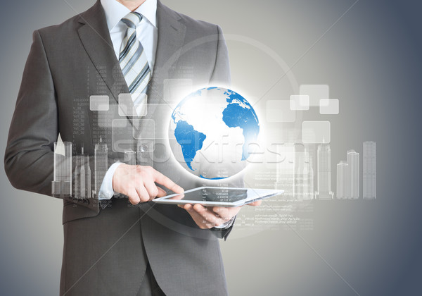 Businessman with tablet and planet Stock photo © cherezoff