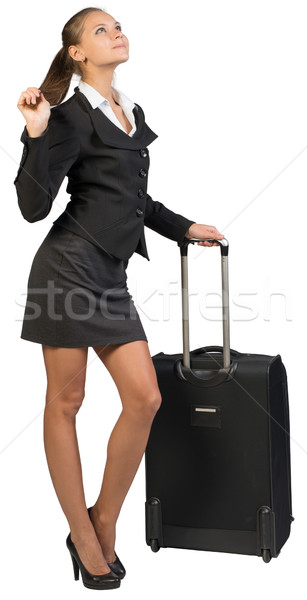 Businesswoman with wheeled suitcase, holding her hair Stock photo © cherezoff