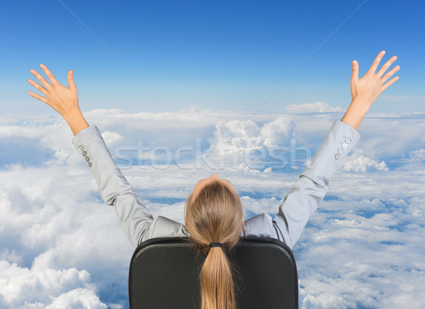 Businesswoman sitting on office chair with her hands outstretched Stock photo © cherezoff