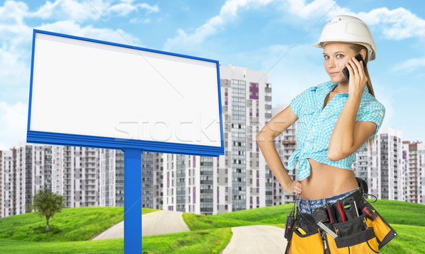 Woman in tool belt using phone. Green hills, road, buildings and billboard as backdrop Stock photo © cherezoff