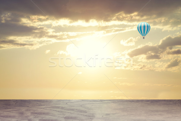Evening sunset. Concrete floor on background of clouds, sun with air balloon Stock photo © cherezoff