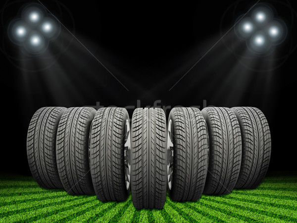 Wedge of new car wheels. Green grass, stripes at bottom and spotlights Stock photo © cherezoff