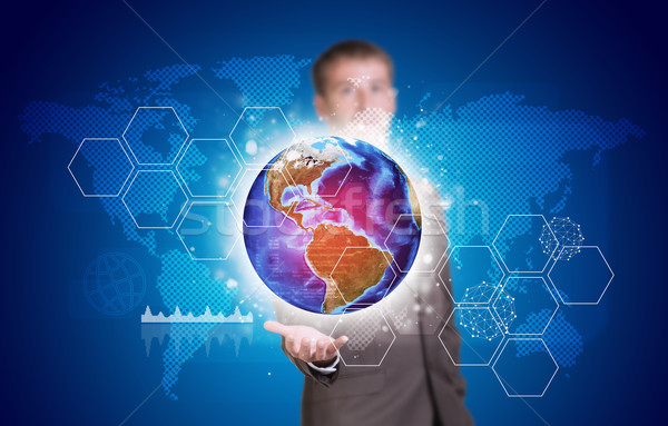 Businessman in suit hold Earth with hexagons and world map Stock photo © cherezoff