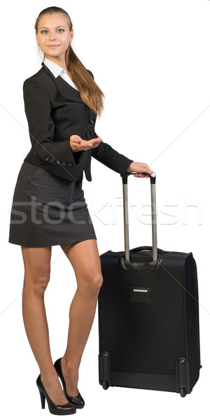 Businesswoman with wheeled suitcase, showing something, looking at camera Stock photo © cherezoff