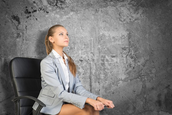 Woman wearing jacket, blouse holding clipboard. Background concrete wall Stock photo © cherezoff