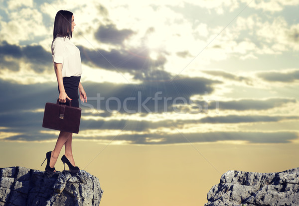 Stock photo: Businesswoman standing on the edge of rock gap