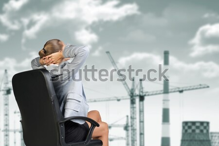 Rear view. Businesswoman relaxed leaned back in chair Stock photo © cherezoff