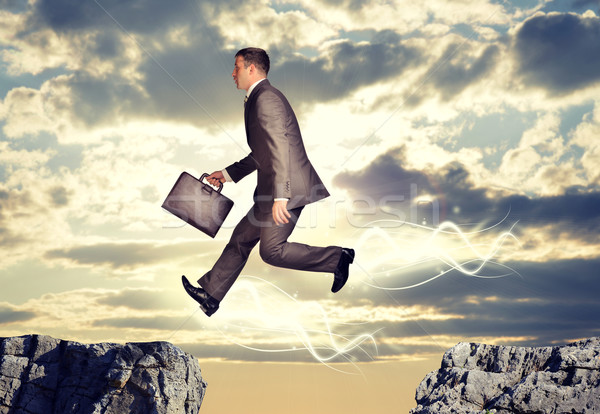 Businessman jumping over abyss Stock photo © cherezoff